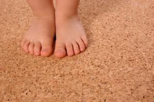 Kinderfüße auf einem Korkboden